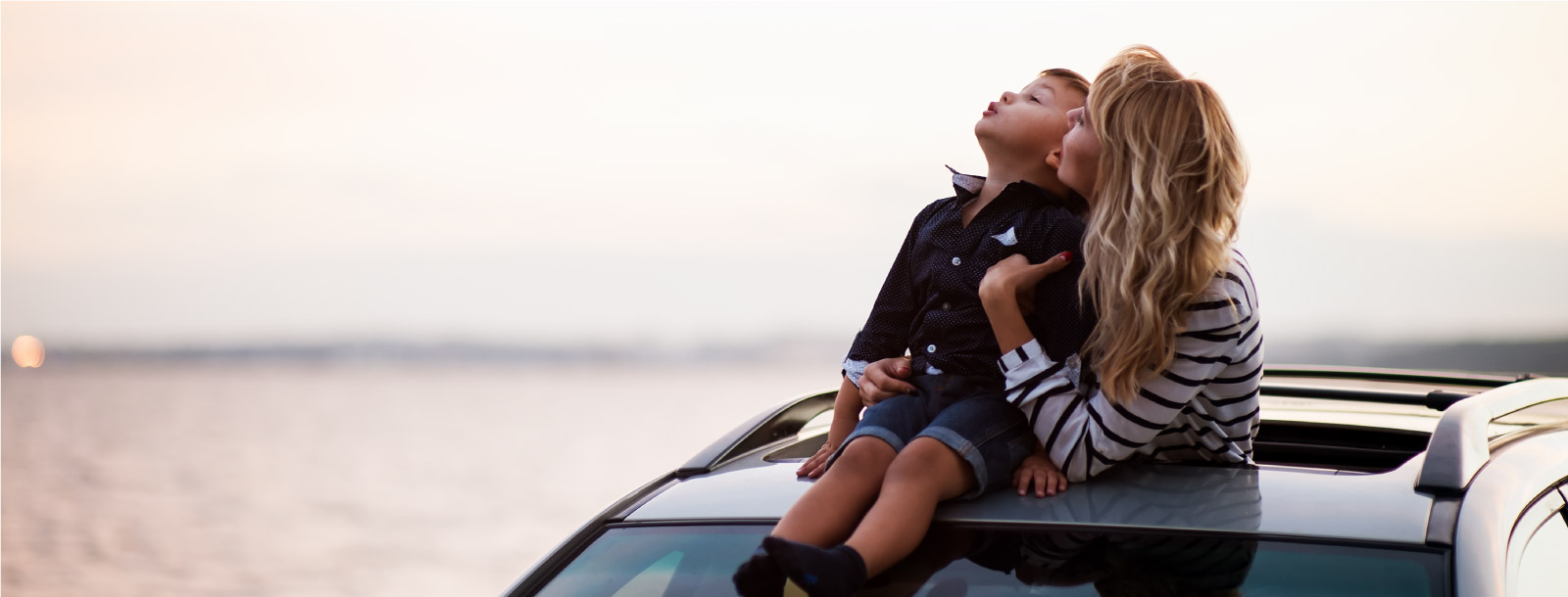 Mother and son out of the sunroof of a car